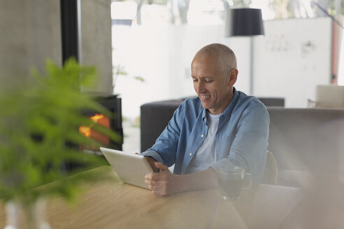Mature man using digital tablet at dining table - HOXF02079