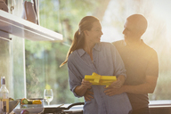Smiling husband surprising wife with gift in sunny kitchen - HOXF02085