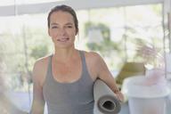 Portrait smiling mature woman holding yoga mat - HOXF02088