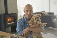Portrait smiling mature man holding cute dog - HOXF02091