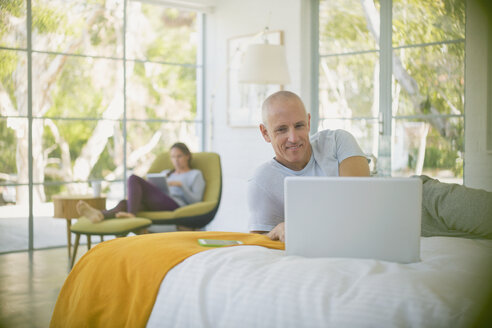 Mature couple relaxing, using laptop and digital tablet in bedroom - HOXF02094
