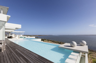 Sunny, tranquil modern luxury home showcase exterior infinity pool with ocean view under blue sky - HOXF02097