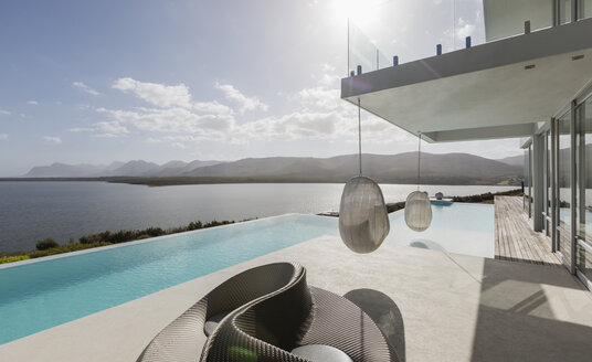 Sunny modern luxury home showcase exterior with infinity pool and ocean view - HOXF02115