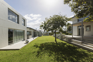 Sunny modern luxury home showcase exterior with grass courtyard - HOXF02127