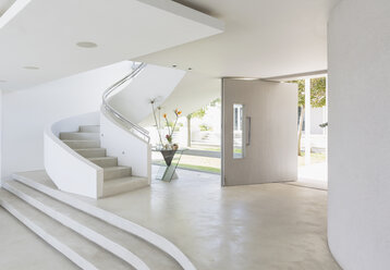 White foyer and spiral staircase in modern luxury home showcase interior - HOXF02139