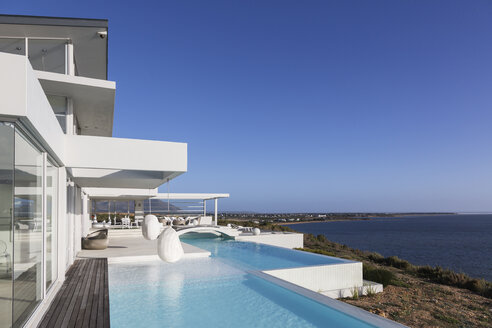 Sunny, tranquil modern luxury home showcase exterior with infinity pool and ocean view under blue sky - HOXF02142