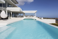 Sunny, tranquil modern luxury home showcase exterior swimming pool and patio - HOXF02148