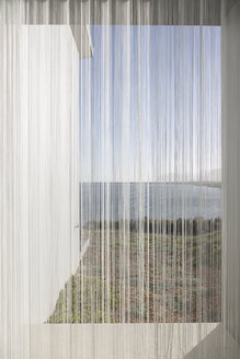 Gauze curtains in sunny, tranquil window with ocean view - HOXF02151