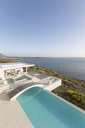 Sunny, tranquil modern luxury home showcase infinity pool with footbridge and ocean view under blue sky - HOXF02154