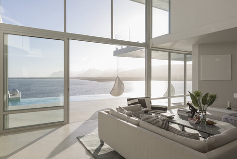 Sunny, tranquil modern luxury home showcase interior living room with ocean view - HOXF02157