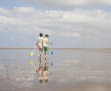 Brother and sister walking with shovels in wet sand on sunny summer beach - HOXF02190