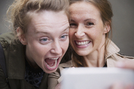 Playful, laughing women friends taking selfie with camera phone - HOXF02202