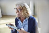 Smiling senior woman using digital tablet - HOXF02241