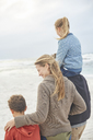 Family walking on winter beach - HOXF02250