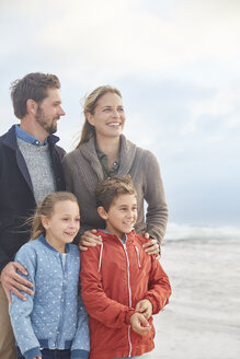 Smiling family on winter beach - HOXF02259