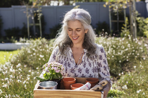 Smiling mature woman carrying gardening tray in sunny garden - HOXF02289