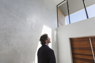 Pensive businessman looking up at window - HOXF02295
