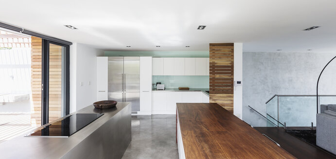 Modern, minimalist home showcase interior kitchen with wood and stainless steel counters - HOXF02316
