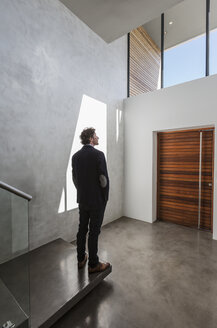 Pensive businessman standing in modern home showcase interior foyer - HOXF02328