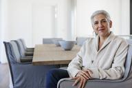 Portrait confident mature woman sitting at dining table - HOXF02331