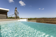 Businessman standing on luxury sunny patio with infinity pool, looking at view - HOXF02349