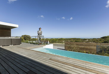 Businessman on sunny modern, luxury patio with infinity pool - HOXF02355
