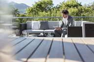 Businessman using digital tablet on sunny luxury balcony patio sofa - HOXF02361