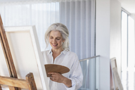 Smiling mature woman with palette painting at canvas on easel - HOXF02370