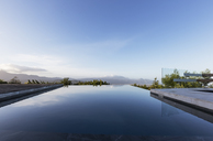 Tranquil luxury infinity pool with mountain view below blue sky - HOXF02373