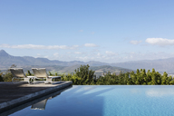 Luxury infinity pool and lounge chairs with mountain view under sunny, blue sky - HOXF02397