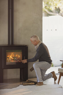 Man placing firewood in wood stove - HOXF02406