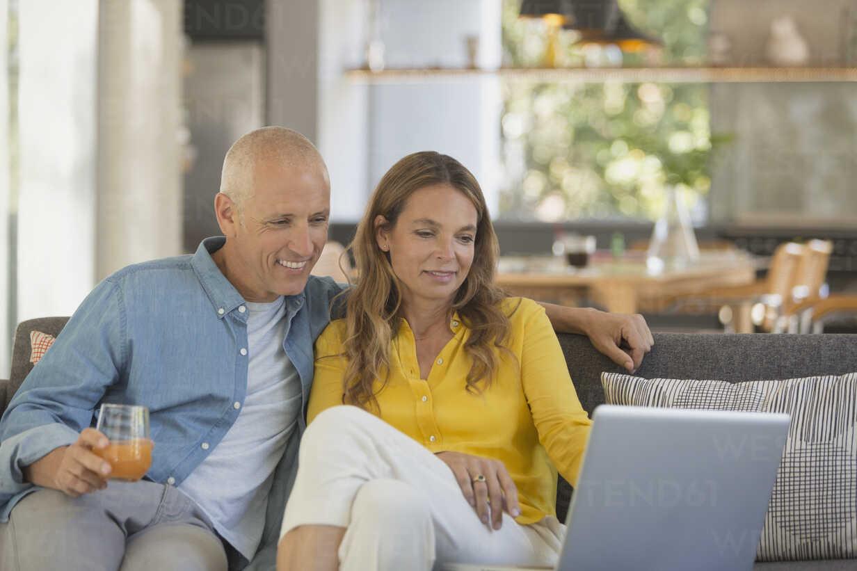 Couple relaxing, using laptop on living room sofa - HOXF02418 - Tom Merton/Westend61