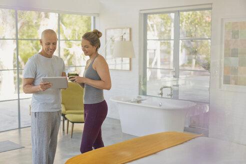 Couple in pajamas using digital tablet in luxury hotel bedroom - HOXF02436