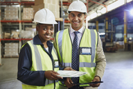 Portrait smiling manager and worker with paperwork in distribution warehouse - HOXF02445