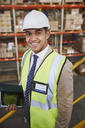 Portrait smiling manager with digital tablet in distribution warehouse - HOXF02448