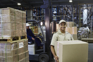 Portrait smiling worker carrying cardboard box at distribution warehouse loading dock - HOXF02451