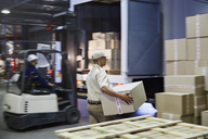 Workers and forklift loading cardboard boxes onto trucks at distribution warehouse loading dock - HOXF02454