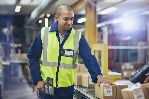 Worker with scanner scanning and processing boxes on conveyor belt in distribution warehouse - HOXF02463