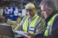 Workers with clipboard and laptop working in distribution warehouse - HOXF02466
