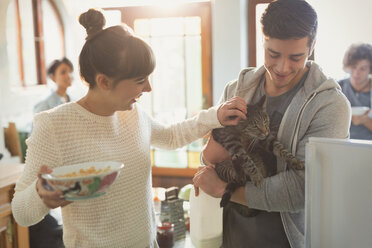Young couple petting cat in kitchen - HOXF02496