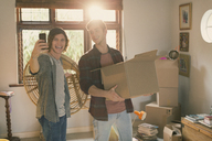 Young men roommates taking selfie moving boxes in apartment - HOXF02517