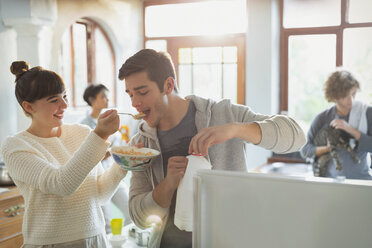 Young woman feeding boyfriend cereal in apartment kitchen - HOXF02520