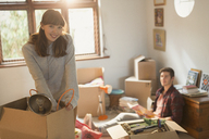Portrait smiling young couple unpacking moving boxes in apartment - HOXF02526