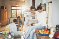 Smiling young couple using digital tablet in kitchen - HOXF02568