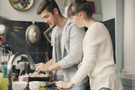 Young couple cooking in kitchen - HOXF02571