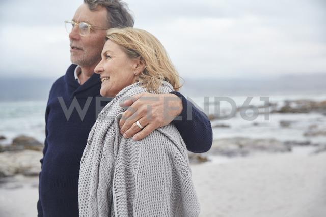 Affectionate senior couple hugging on winter beach - HOXF02601