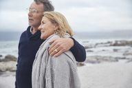 Affectionate senior couple hugging on winter beach - HOXF02601