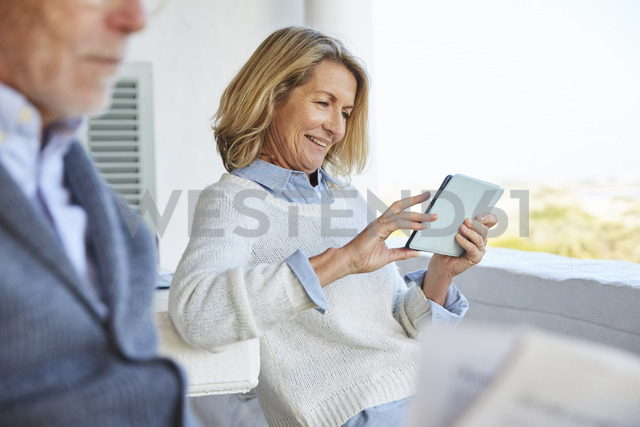 Senior woman using digital tablet on patio - HOXF02604