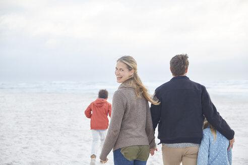 Portrait happy family walking on winter beach - HOXF02643
