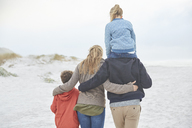 Affectionate family walking on winter beach - HOXF02652